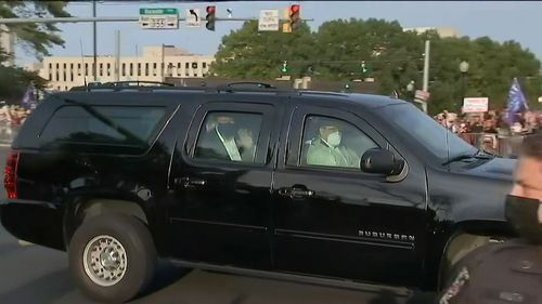 Donald Trump drives past supporters