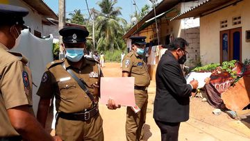 Sri Lankan magistrate Wasantha Ramanayake, right and police officers inspect outside a house where a nine-year-old girl was canned to death in Delgoda, Sri Lanka.
