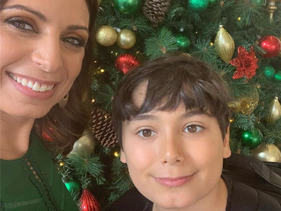 Jo Abi and her son standing in front of a Christmas tree