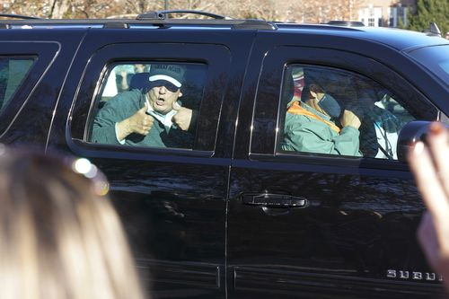 President Donald Trump gives two thumbs up to supporters as he departs after playing golf at the Trump National Golf Club