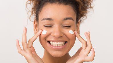 Skin care. Laughing girl applying moisturising cream on her face over white background