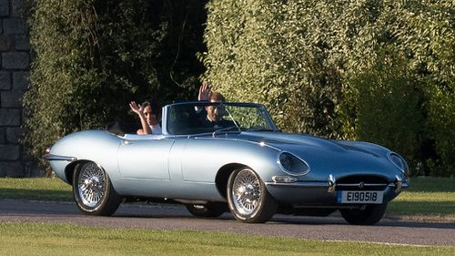 The newlyweds were snapped leaving Windsor Castle in a silver-blue Jaguar E-Type electric car followng a day of glitz and glamour.