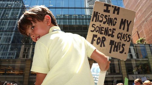 A young boy protests against climate change in Martin Place.