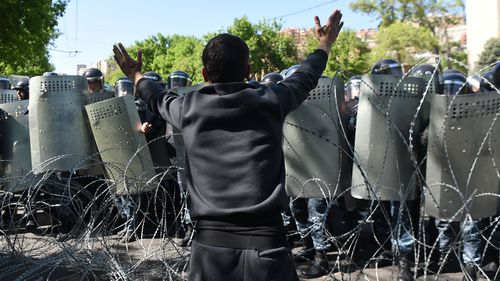 A man gestures as police blocks a street during an opposition rally against nomination of former Armenian president Serzh Sargsyan to the post of prime minister in Yerevan, Armenia. (AAP)