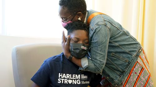 Julian Boyce, 14, gets a hug from his mother, Satrina Boyce, after he received his first Pfizer COVID-19 vaccination dose in New York.