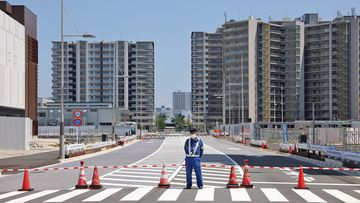 A security man stands on guard at the entrance to the Tokyo 2020 Olympic Village in Harumi
