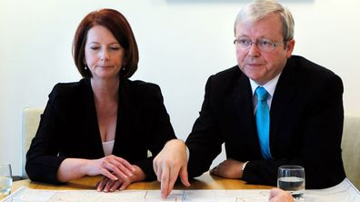 Then-prime minister Julia Gillard with former prime minister Kevin Rudd discuss their election campaign on August 7, 2010. (Getty)