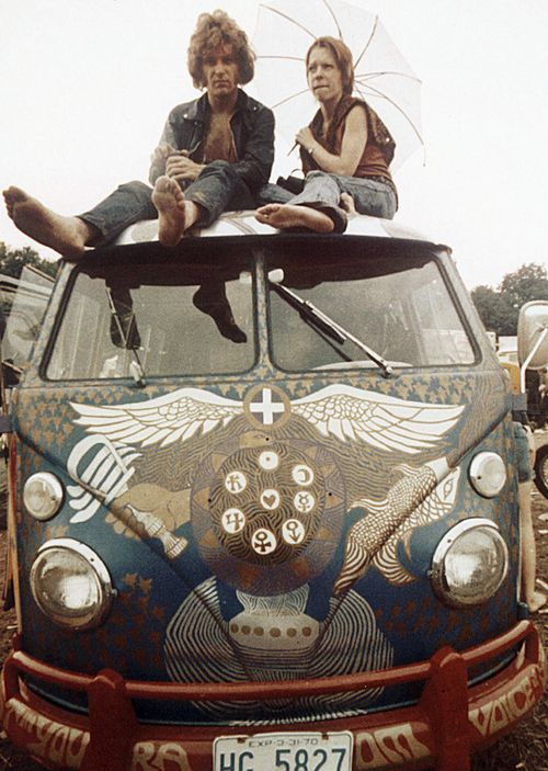 Concert-goers sit on the roof of a Volkswagen bus at the Woodstock Music and Arts Fair at Bethel, New York. The three-day concert attracted hundreds of thousands of people, and became a landmark cultural event of the late '60s.