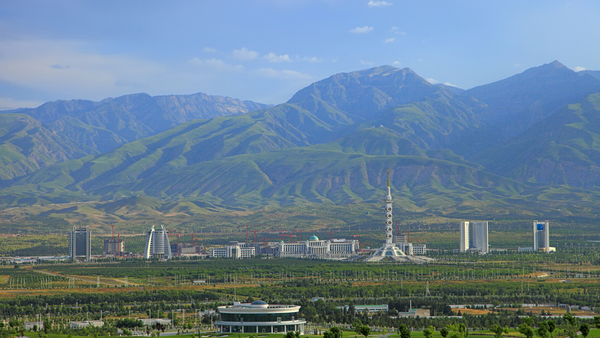 Ashgabat, Turkmenistan: Constitution monument and government buildings on Archabil avenue with mountains in the background