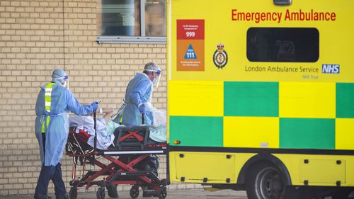 NHS workers in PPE take a patient with an unknown condition to an ambulance at Queens Hospital on April 21, 2020 in London, England