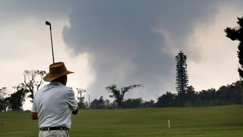 A man plays golf as as ash from the summit crater of Kilauea volcano rises in the background.