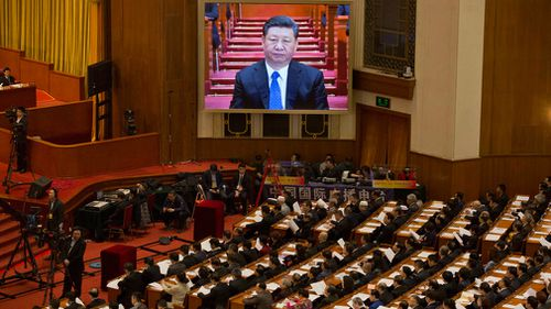 Chinese President Xi Jinping is seen on a large screen at the opening session of the Chinese People's Political Consultative Conference. (AAP)