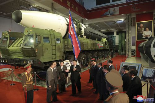 Kim Jong Un, centre, speaks in front of what the North says an intercontinental ballistic missile displayed at an exhibition of weapons systems.