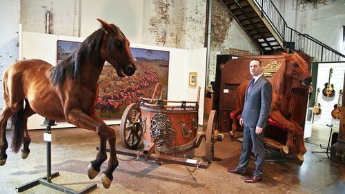 """John Keats from Sotheby's Australia stands with props from the film """"Gladiator"""" owned by actor Russell Crowe. (AAP)"""