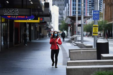 A woman wearing a face mask walks along George street in Sydney's CBD on April 8. Many people are working from home to help stop the spread of the coronavirus.