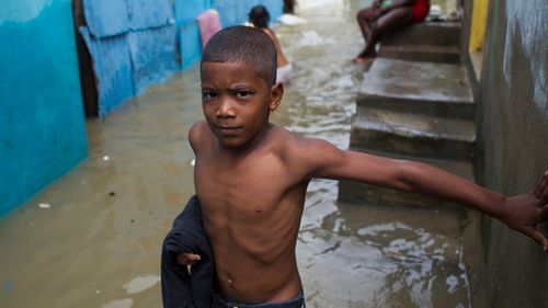 A boy in the flooded neighbourhood of La Puya, in Santo Domingo on Tuesday after the passage of Hurricane Matthew through Hispaniola - the island that the Dominican Republic shares with Haiti. (AFP)