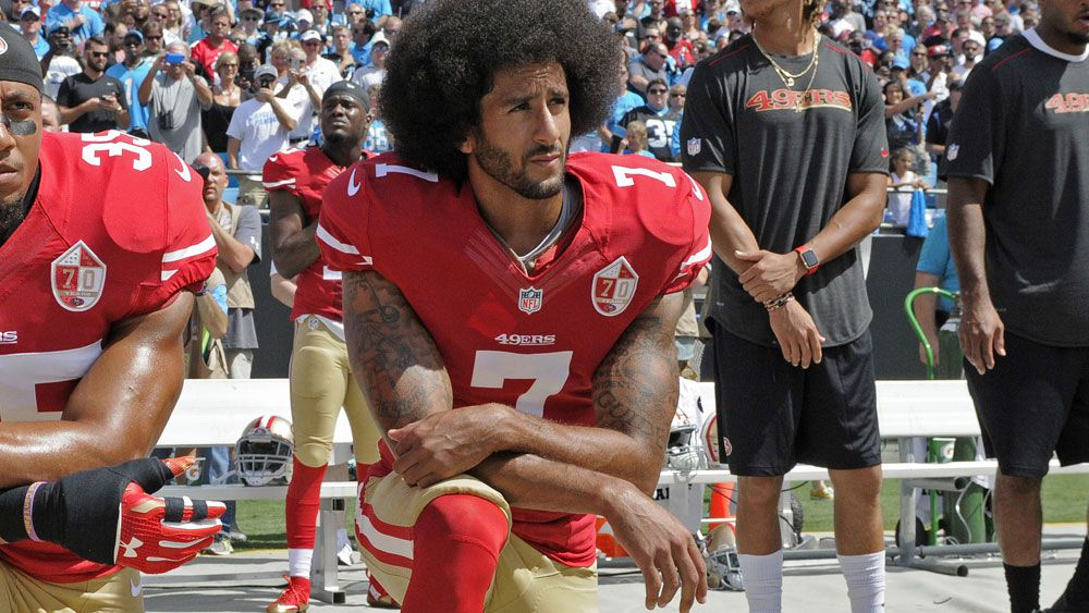 Colin Kaepernick kneels during the national anthem. (AAP)