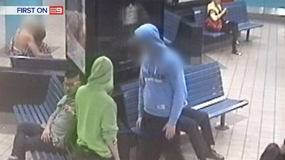 Members of the gang talk to and distract a seated man, scoping out the situation. (9NEWS)