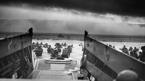 American troops wade ashore under heavy fire on Omaha Beach, Normandy, on June 6, 1944.