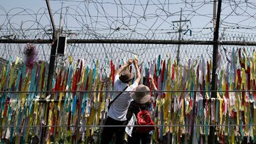 Visitors hang a ribbon on a wire fence decorated with other ribbons at the Imjingak Pavilion in Paju, South Korea, Tuesday, June 9, 2020. (AP Photo/Lee Jin-man)