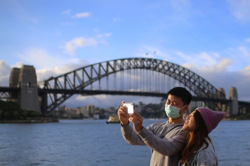 People wear face masks in front of the Sydney Harbour Bridge in Sydney, Monday, March 9, 2020.