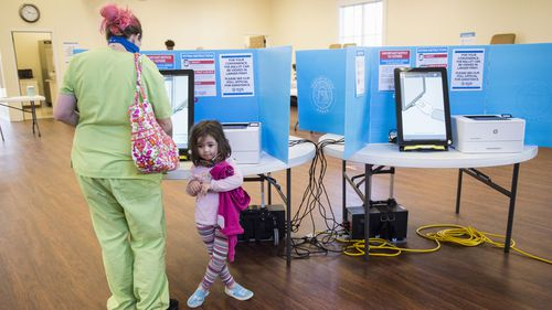 Scarlette Martin, 4, waits as her mum, Jocelyn Martin, casts her vote in Georgia's US Senate runoff election.