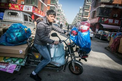 A Chinese vendor rides a motorcycle loaded with Christmas decorations and dolls on a road in Yiwu city.