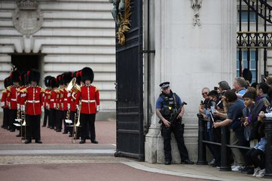 Members of the public wait outside Buckingham Palace to watch the Changing of the Guard ceremony on August 23, 2021 in London, England. The event marks the return of one of the city's top tourist attractions which had not been performed since March 2020.