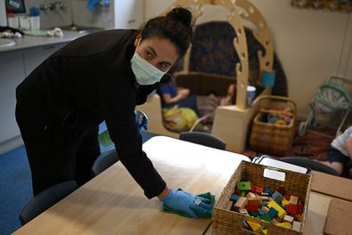 Early childhood educator Josephine wipes down tables and bench tops with disinfectant at the Robertson Street Kindy Childcare Centre in Helensburgh south of Sydney, Friday, April 3, 2020.