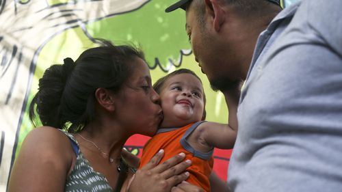 Adalicia Montecino kisses her year-old son Johan Bueso Montecinos, who became a poster child for the U.S. policy of separating immigrants and their children, as Johan touches his father Rolando Bueso Castillo's face, in San Pedro de Sula, Honduras. (AAP)