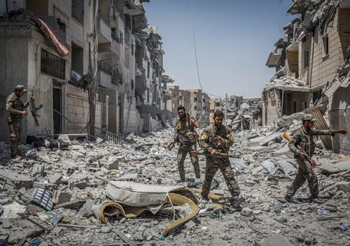 Soldiers of the Syrian Democratic Forces (SDF) move through debris at the front line in the Al Dariya neighborhood in western Raqqa, Syria, 24 July 2017. (AFP)
