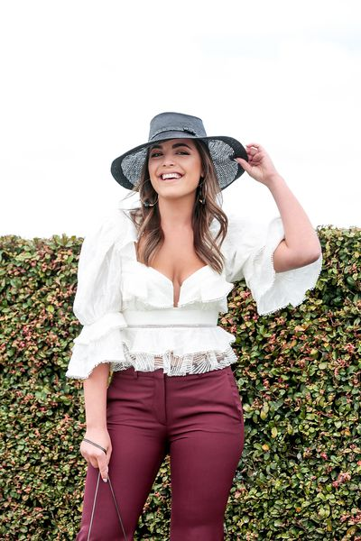 Olympia Valance dared to bare in maroon pants and white lace top and black straw hat. It's the races after all.