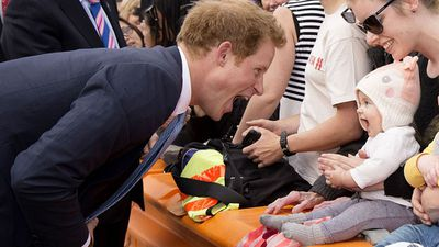 Prince Harry greets a baby during his New Zealand tour, May 2015
