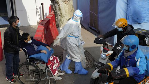 A medical worker in protector overall escorts a patient in wheelchair from the fever screening department of the Tongji Hospital which was at the frontline of the China's fight against the coronavirus in Wuhan in central China's Hubei province on Friday, Jan. 15, 2021