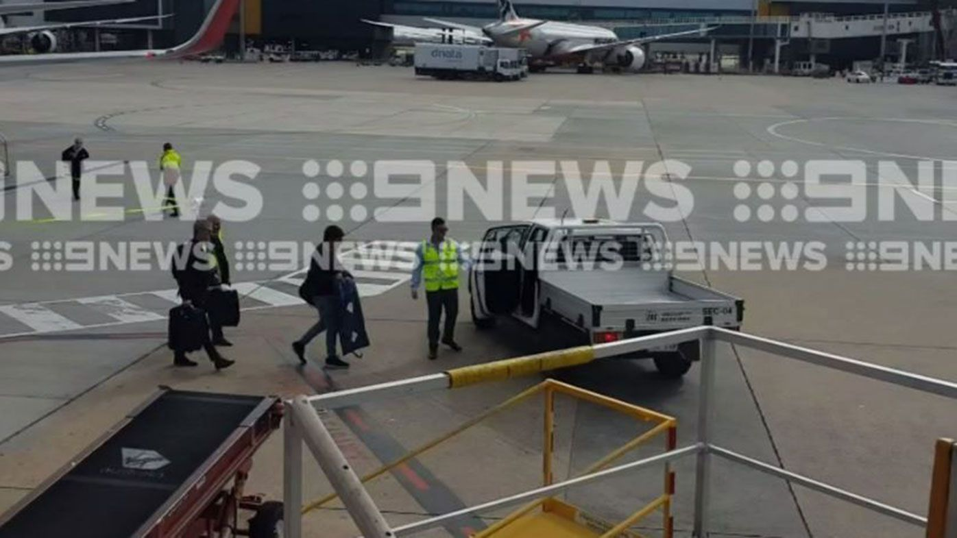 Andrew Gaff is ushered into a waiting ute at Melbourne Airport