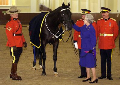 Queen Elizabeth pats James,  the horse that presented as a gifted to the Queen by members of the Royal Canadian Mounted Police in 1998.