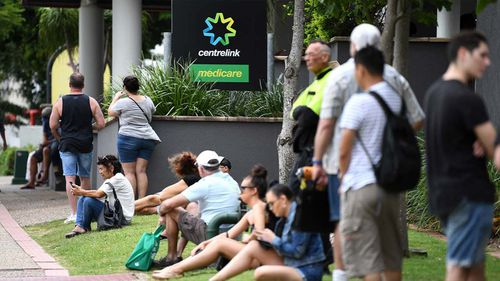 People are seen in long queues outside the Centrelink office in Southport on the Gold Coast, Monday, March 23, 2020.