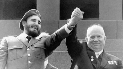 In this May 1, 1963  photo, Cuba's leader Fidel Castro, left, and Soviet Premier Nikita Khrushchev clasp hands at the Lenin mausoleum in Moscow's Red Square on May Day in Moscow, Russia. (AAP)
