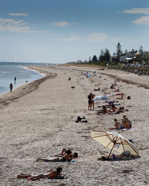 Adelaide residents flocked to Henley Beach today as temperatures exceeded 34 degrees for the third day in a row. (AAP)