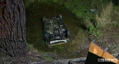The car rolled into a creek after the impact. (9NEWS)