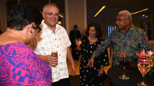 Prime Minister of Fiji Frank Bainimarama points to Australian Prime Minister Scott Morrison's sulu vaka taga as he arrives in traditional Bula dress with his wife Jenny to an official dinner.