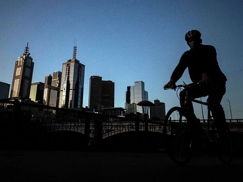 A man rides his bike along a very quiet Southbank in Melbourne, Australia.