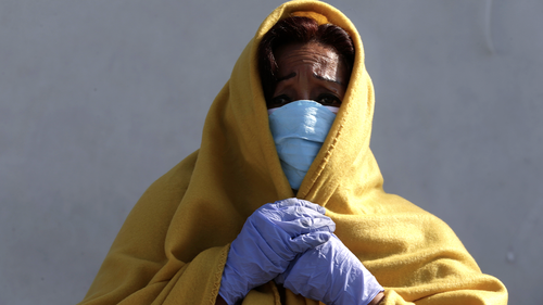 A woman wearing a face mask, plastic gloves, and a blanket waits to be tested for COVID-19 outside the emergency door at Almenara Hospital in Lima, Peru, Friday, April 24, 2020. (AP Photo/Martin Mejia)