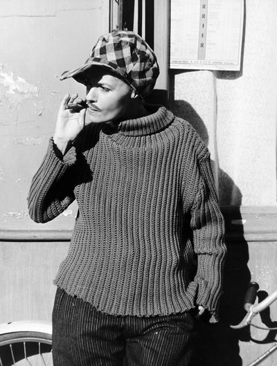 Jeanne Moreau in boy drag wearing a cap, moustache, and smoking a cigar in the 1962 French film, <em>Jules et Jim</em>.