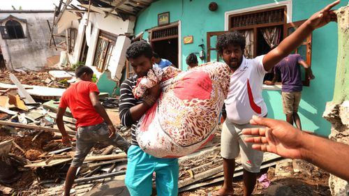 Survivors move items from destroyed homes now buried under the collapsed garbage mountain in Colombo, Sri Lanka. (AFP)