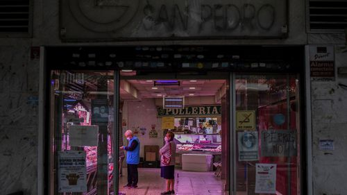 Two customers wearing face masks to prevent the spread of the coronavirus inside a food market in the southern neighbourhood of Vallecas in Madrid, Spain, Friday, October 2, 2020.
