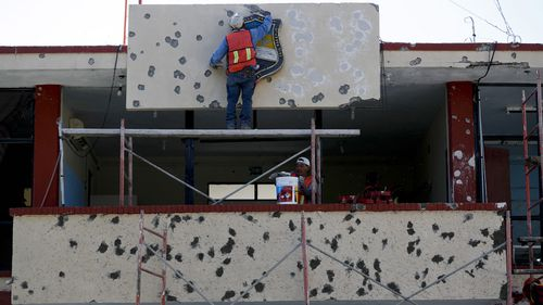 Workers repair the facade of City Hall riddled with bullet holes in Villa Union.