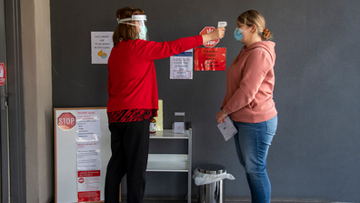 A patient has her temperature checked before a medical clinic during lockdown due to the continuing spread of the coronavirus in Melbourne, Thursday, Aug. 6, 2020. (AP Photo/Andy Brownbill)