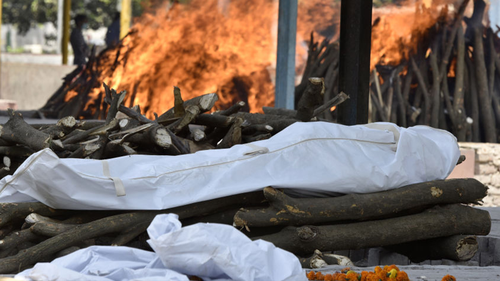 The body of a person who died of COVID-19 is placed on a pyre while others burn in the background at Sector 94, on April 21, 2021 in Noida, India.