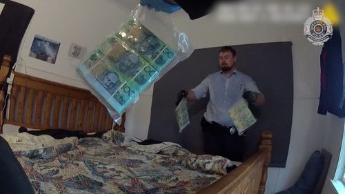 Police have been captured pulling out thousands of dollars in cash out of a north Queensland mattress following a major drug raid that saw six people arrested this past weekend.